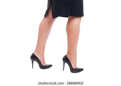 Sexy business woman legs walking on white studio background