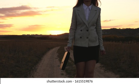 sexy Business woman walking along a country road with a briefcase in hand, the sun shimmers at sunset. Sexy business girl working in countryside. beautiful girl travels the countryside.