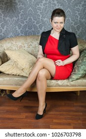 sexy businesslady wearing red dress and black jacket rests on a sofa