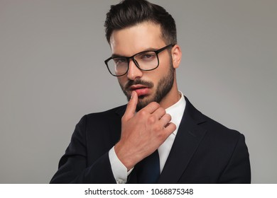 sexy businessman flirting with thumb on lips, looking sensually on grey background