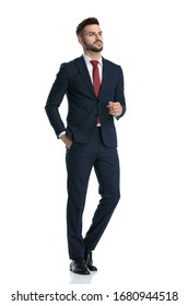 sexy businessman wearing navy suit walking with hand in pocket and posing with tough attitude on white studio background