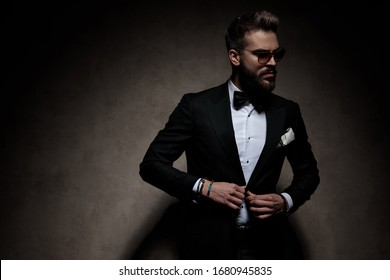 sexy businessman wearing sunglasses standing and unbuttoning his jacket while looking aside dramatic on dark studio background