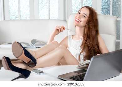 Sexy businesswoman working at the office with legs and heels on the table