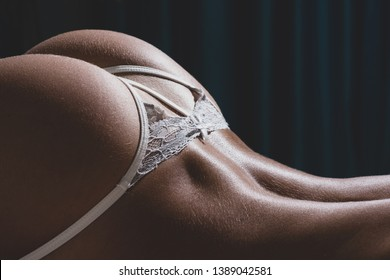 Sexy buttocks white lingerie. Attractive female ass. Erotic massage. Perfect buttocks. Waiting for you. Escort service. Desire concept. Sexy woman relaxing. Buttocks smooth skin. Flexible female body.