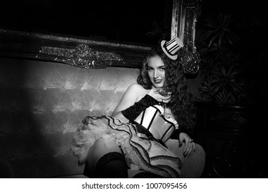 Sexy cabaret woman in corset posing in vintage armchair. Burlesque lingerie in fashion interior. black and white