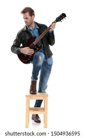 sexy casual man with black leather jacket is standing with one leg on chair and the other down while playing the guitar passionate and looking to a side on white studio background