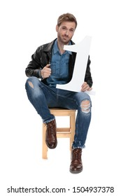 sexy casual man with black leather jacket is sitting on a wooden chair  with a number one in his hand while fixing his jacket serious on white studio background