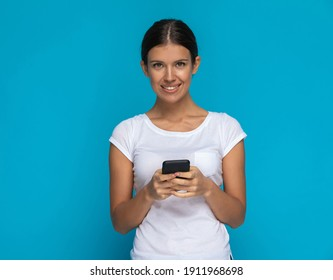 sexy casual woman texting on her phone and smiling against blue background