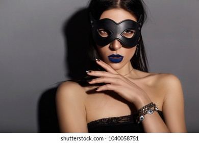 Sexy caucasian brunette woman wearing black top, leather cat mask and blue lip make up. BDSM dominant theme on a neutral grey background
