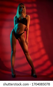 Sexy caucasian female model wearing lingerie standing in shadows, isolated on dark red with blue light. Fashionable woman with perfect body posing in shadows on high heels, holding hand behind back.