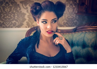Sexy Caucasian model looking like a vampire with a black stiletto nail between the teeth and looking away on a couch, having sculpting make-up and cocktail dress. Maleficent lookalike retro concept