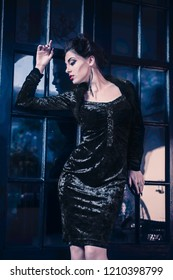 Sexy Caucasian woman model like a vampire looking away against a window door, having sculpting make-up and cocktail dress with big cleveage. Maleficent lookalike concept
