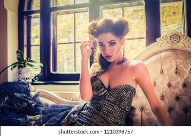 Sexy Caucasian woman model looking like a vampire sitting down on a baroque couch, near the window, in the living room, dressed in a cocktail silver dress. Maleficent lookalike and Halloween concept