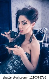 Sexy Caucasian woman model looking like a vampire sitting down and drinking a coffee in the living room, dressed in a cocktail silver dress. Maleficent lookalike and Halloween concept