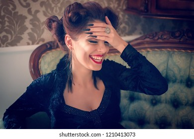 Sexy Caucasian woman model looking like a vampire laughing on a couch, having sculpting make-up and cocktail dress with big cleveage. Maleficent lookalike retro concept