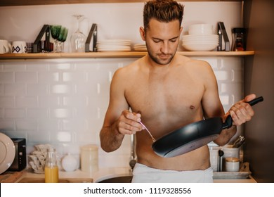 Sexy chef with naked body cooking in the home kitchen