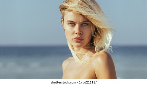 Sexy closeup portrait of attractive blonde female model with beautiful eyes looking into the camera at the beach.