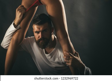 Sexy closeup portrait of handsome brutal bearded male model with beautiful woman legs. Sensual coule and point orgasm. Brutal man l takes off her lingerie. Sexy and sensual copy space