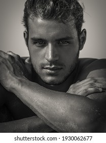 Sexy closeup portrait of handsome topless male model with beautiful eyes looking into camera at the beach. Black and White.