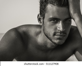 Sexy closeup portrait of handsome topless male model with beautiful eyes on the beach. Black and White.