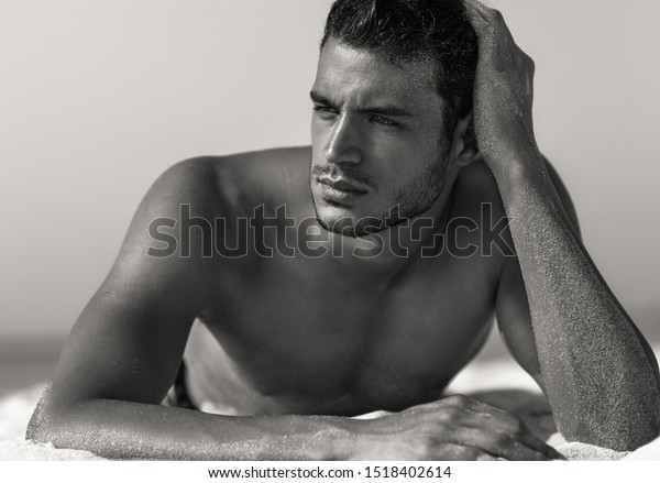 Sexy closeup portrait of handsome topless male model on the beach. Black and White.