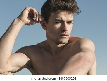 Sexy closeup portrait of topless male model outdoors.