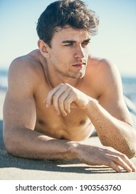 Sexy closeup of topless handsome male model lying on the sand at the beach.