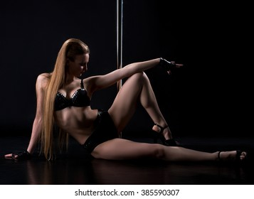 Sexy clubbing dancer posing with pylon in studio