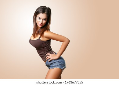 Sexy confident girl posing in studio. Young beautiful slim woman wearing denim shorts, playful flirt pose, isolated on brown background