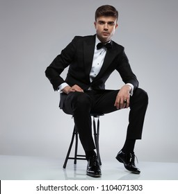 sexy confident man wearing a black tuxedo sitting on a metal chair on light grey background, having a golden ring on his finger