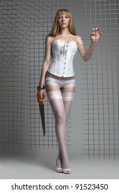 Sexy cool blonde woman posing alongside re-inforcing mesh in a white corset and stockings, holding saw, studio.