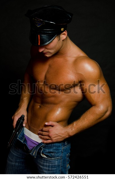 Studio Shot Of Young Muscular Persian Man Reloading Gun