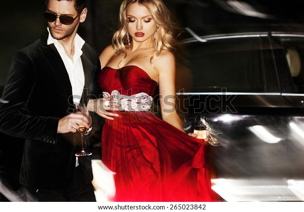 Sexy couple in the car. Hollywood star. Fashionable pair of elegant people at night city street.