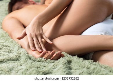 Sexy couple doing erotic massage in bedroom on green blanket. Close-up shot in hands.