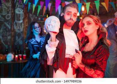 Sexy couple dressed up like vampires for halloween party. Beautiful woman dressed up like a vampire. Sexy man dressed up like Dracula.
