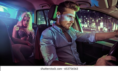 Sexy couple in an elegant car, at night