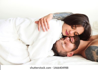 Sexy couple in love smiling while lying on bed together
