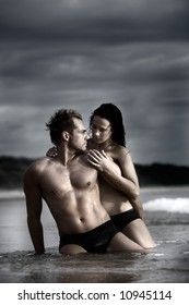 Sexy couple on beach with dark stormy clouds in background