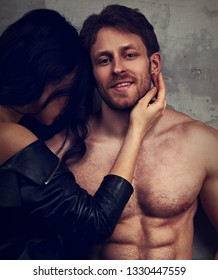 Sexy couple portrait. Beautiful brunette woman hugging her smiling happy man with nude torso with much emotion in dark drama light with dark shadow. Closeup portrait