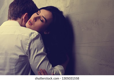 Sexy couple portrait. Man in white shirt kissing his sensual beautiful girlfriend in neck with much emotion. Toned color art portrait