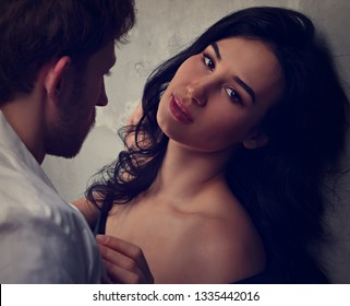 Sexy couple portrait. Man in white shirt hugging his sensual beautiful girlfriend with much emotion. Closeup toned portrait