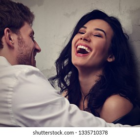 Sexy couple portrait. Man in white shirt looking on his sensual wide laughing beautiful girlfriend with much emotion in dark drama light . Closeup toned portrait