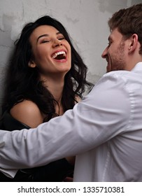 Sexy couple portrait. Man in white shirt looking on his sensual wide laughing beautiful girlfriend with much emotion in dark drama light . Closeup