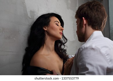 Sexy couple portrait. Man in white shirt sexual toching his sensual beautiful girlfriend neck with much emotion. Closeup portrait