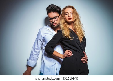 sexy couple pose close to each other in studio background while looking down