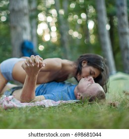 Sexy couple. Couple in a romantic mood lying down outdoors in a park. Man and woman sitting on meadow at nature and kissing. Girl and boy looking at the landscape and enjoying vacation. Having sex.