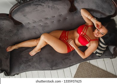 Sexy curvy tanned woman in red lingerie with decorative straps on sofa.