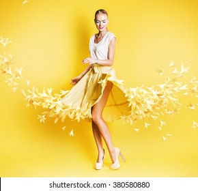sexy dancing blond woman in yellow skirt of flowers on yellow background