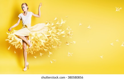 sexy dancing woman in yellow skirt with flowers on yellow background