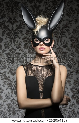 Erotic easter female portrait dark very sexy blonde curly hair style black lingerie wearing bizarre dark bunny mask